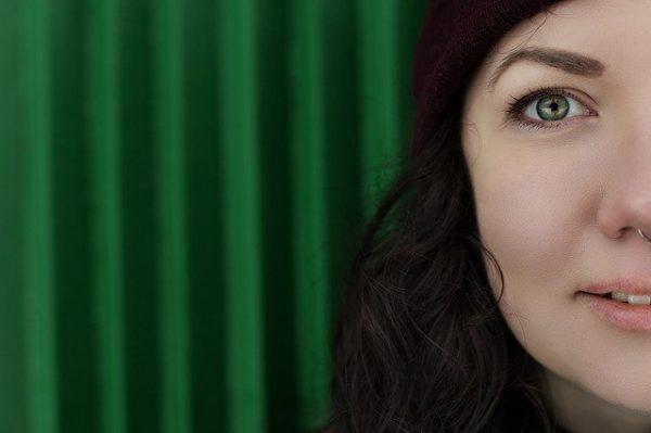 Halbes Porträt einer Frau mit reiner Haut vor grüner, welliger Wand.